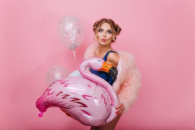 Attraktives lockiges mädchen mit trendiger frisur in flauschigen weichen kleidern, die mit kussgesichtsausdruck aufwerfen. nette hübsche frau im rosa mantel, die spaß mit bunten luftballons der partei lokalisiert auf heller wand hat