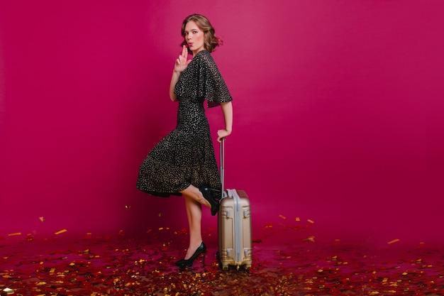 Attraktives lockiges weibliches modell mit gepacktem koffer, der auf einem bein steht