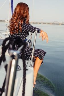 Attraktives mädchen auf einer yacht am sommertag. nahaufnahme des modeporträts der atemberaubenden romantischen frau, die yacht aufwirft. trägt ein elegantes kleid, sommer-outfit. blauer himmel. sonnenuntergang