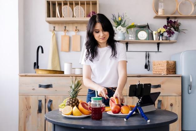 Attraktives mädchen bereitet frucht smoothies zu