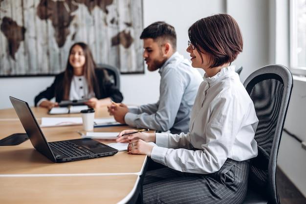 Attraktives mädchen, das an laptop beim treffen ihres personals arbeitet