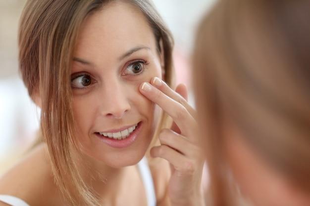 Attraktives mädchen, das anti-aging-creme auf ihr gesicht aufträgt