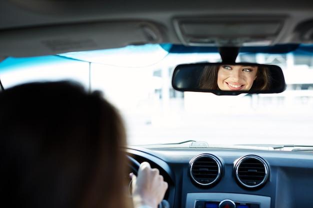 Attraktives mädchen, das blaues hemd trägt, das im neuen automobil sitzt, im verkehr, im porträt feststeckt, neues auto kauft, fahrerin, autospiegelansicht.