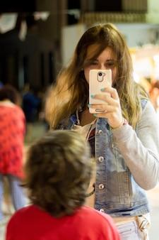 Attraktives mädchen, das ein foto mit einem smartphone macht