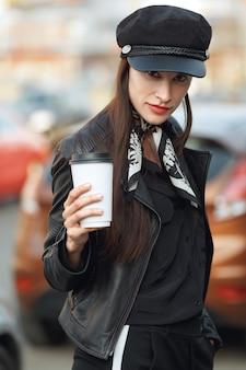 Attraktives mädchen, das entlang die straße mit tasse kaffee geht