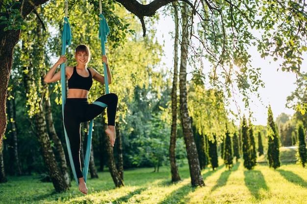 Attraktives mädchen, das herausfordernde akrobatische übungen auf einer hängematte tut. yoga ist ein lebensstil. fliegen yoga.