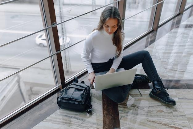 Attraktives mädchen, das mit laptop und sachen im flughafenterminal oder im büro auf boden arbeitet. reiseatmosphäre oder alternative arbeitsatmosphäre.