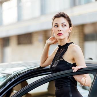 Attraktives mädchen, das nahe dem auto steht