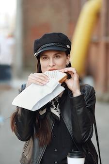 Attraktives mädchen, das sandwich auf der straße isst