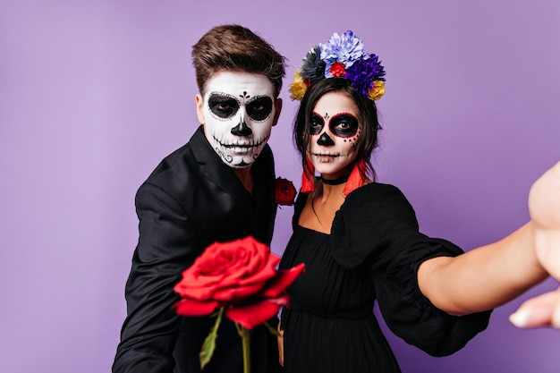 Attraktives mädchen, das sanft lächelt, während es im karnevalskostüm aufwirft. brünette freudige frau, die selfie in halloween mit freund macht.