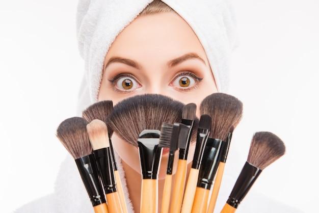 Attraktives mädchen, das sich hinter make-up-pinseln versteckt
