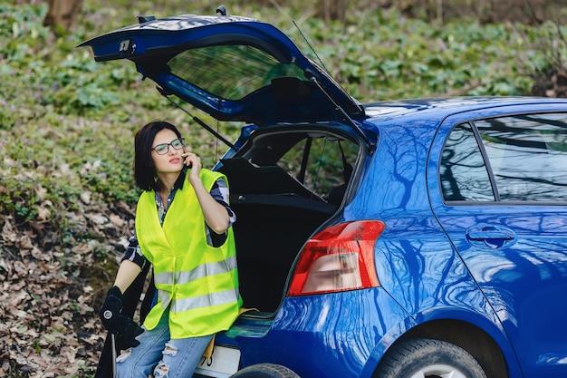 Attraktives mädchen, das telefonisch nahe auto auf straße in der sicherheitsjacke spricht