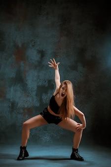 Attraktives mädchen, das twerk iat das blau tanzt