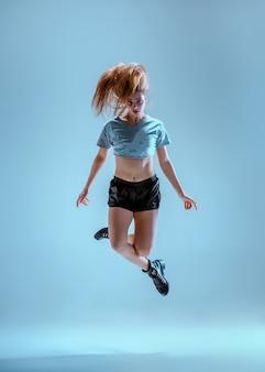 Attraktives mädchen, das twerk iat den blauen studiohintergrund tanzt