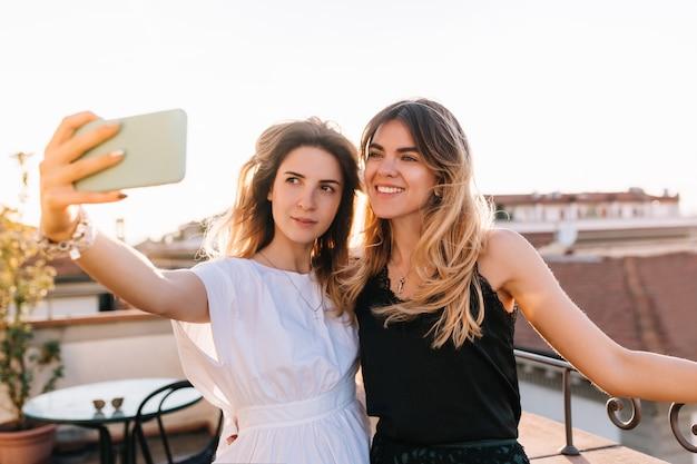 Attraktives mädchen, das weißes kleid und trendige accessoires trägt, die selfie mit bester freundin im morgencafé im freien nehmen