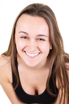 Attraktives mädchen im glücklichen süßen gesicht des jungen frauenporträts, das auf weiß lächelt