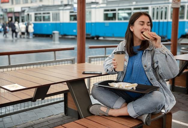 Attraktives mädchen im lässigen stil isst einen burger mit kaffee auf der sommerterrasse eines cafés.