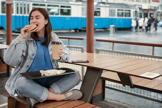 Attraktives mädchen im lässigen stil isst einen burger mit kaffee auf der sommerterrasse eines cafés