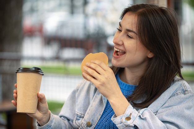 Attraktives mädchen im lässigen stil isst einen burger mit kaffee auf der sommerterrasse.