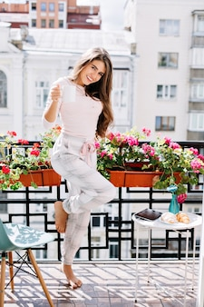 Attraktives mädchen im pyjama auf balkon umgeben blumen in der stadt. sie hat lange haare, hält eine tasse und lächelt.