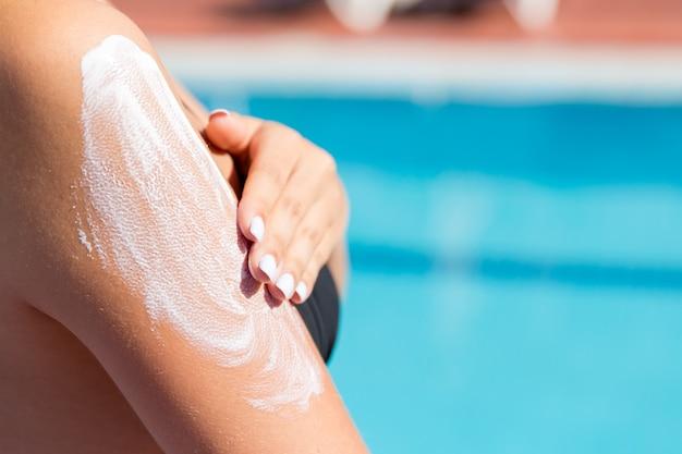 Attraktives mädchen im sonnenhut, das sonnencreme auf der schulter am pool aufträgt. sonnenschutzfaktor im urlaub, konzept.