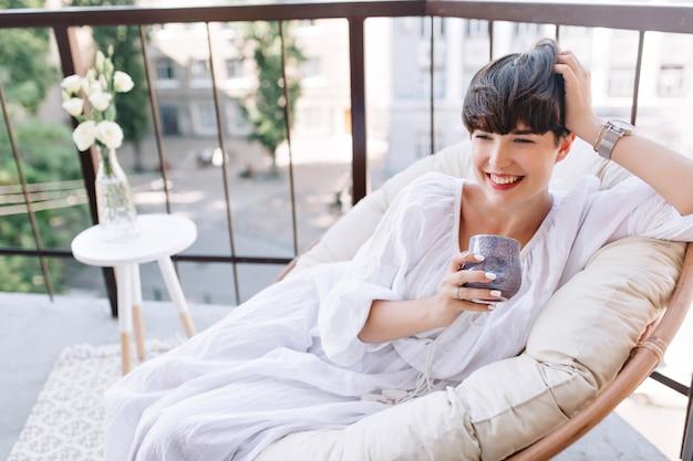 Attraktives mädchen im weißen sommerkleid, das auf sofa auf terrasse mit tasse kaffee und lachen liegt