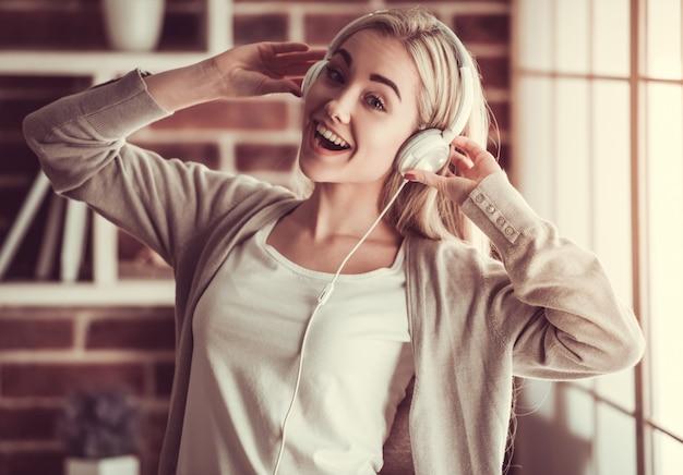 Attraktives mädchen in den kopfhörern hört musik.