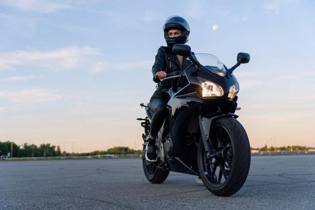 Attraktives mädchen in der schwarzen lederjackenhose und im helm auf parkplätzen im freien reitet auf stilvollem