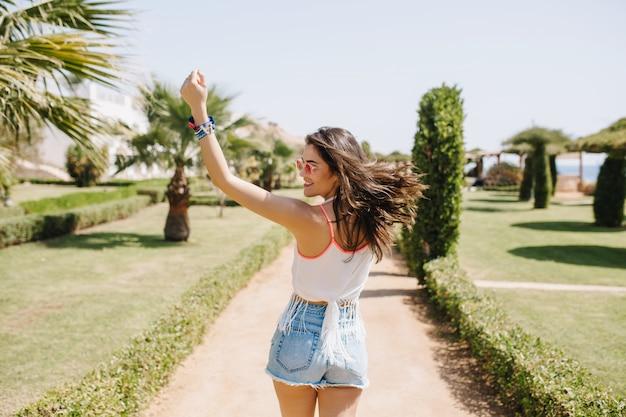 Attraktives mädchen in guter form lustiges tanzen mit den haaren, die winken und lachen und sommerferien im exotischen land genießen. porträt der lächelnden jungen frau der brünetten in der trendigen sonnenbrille, die im park läuft.