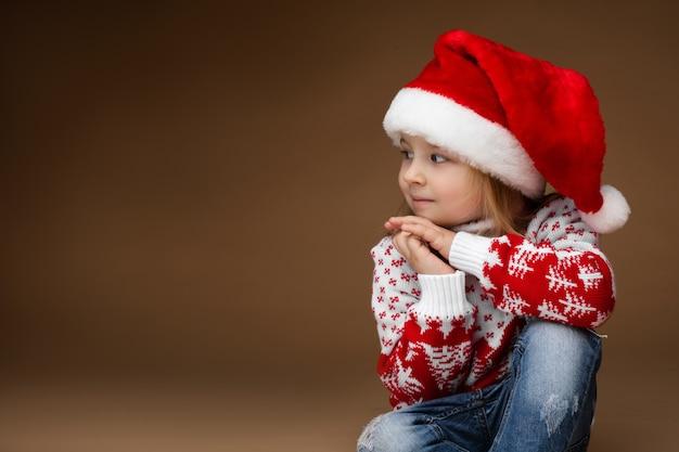 Attraktives mädchen in kuscheliger kleidung und weihnachtsmütze sitzt auf dem boden, bild lokalisiert auf braunem hintergrund