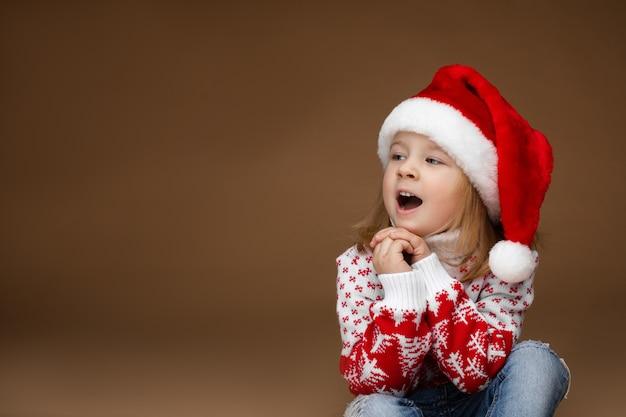 Attraktives mädchen in kuscheliger kleidung und weihnachtsmütze sitzt auf dem boden mit offenem mund, bild lokalisiert auf braunem hintergrund