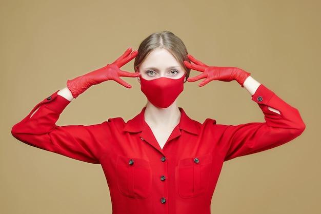 Attraktives mädchen in roten handschuhen und maske. das konzept der prävention von covid 19 coronavirus. fotosession im studio auf gelbem grund
