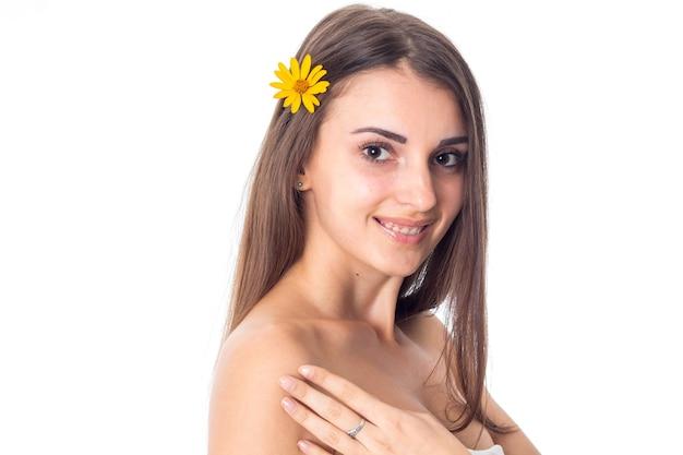 Attraktives mädchen kümmert sich um ihre haut mit gelber blume im haar isoliert auf weißem hintergrund. gesundheitskonzept. konzept der körperpflege. junge frau mit gesunder haut.