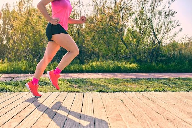 Attraktives mädchen läuft. schließen sie beim lauftechniktraining füße und beine, um verletzungen zu vermeiden. rosa hemd und turnschuhe. holzweg.
