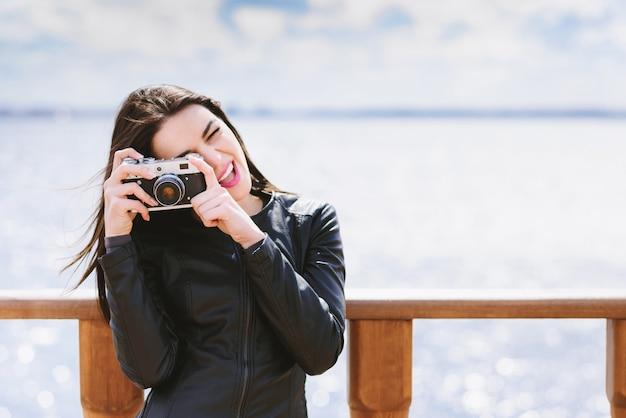 Attraktives mädchen macht fotos mit einer alten kamera