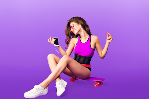 Attraktives mädchen mit dem langen lockigen haar in der rosa sonnenbrille, die auf skateboard auf lila hintergrund im studio kühlt. sie trägt einen badeanzug und hört energielieder mit kopfhörern.