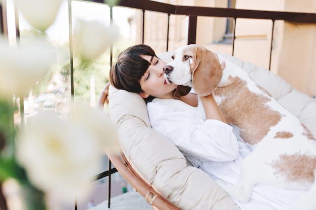 Attraktives mädchen mit dunklen kurzen haaren, die mit liebe beagle hund küssen, der wegschaut