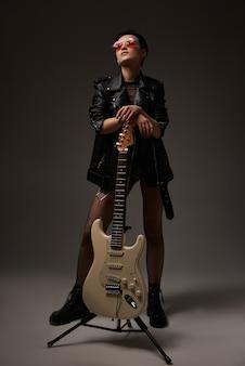 Attraktives mädchen mit einer e-gitarre in einer lederjacke und in der roten brille im studio auf einem weißen hintergrund