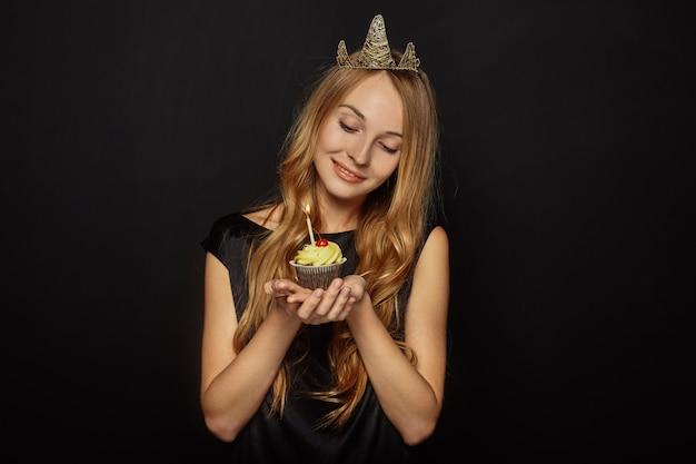 Attraktives mädchen mit einer krone und einem kleinen kuchen