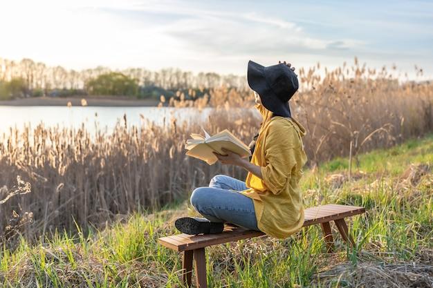 Attraktives mädchen mit hut liest ein buch in der natur bei sonnenuntergang