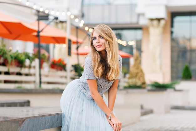 Attraktives mädchen mit langen blonden haaren im blauen tüllrock, der sich auf betonbank auf straße stützt. sie schaut zur kamera.