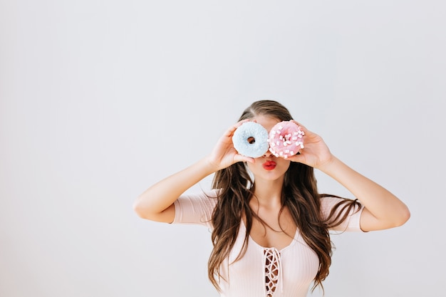 Attraktives mädchen mit langen brünetten haaren, die bunte donuts gegen ihre augen halten. freudige junge frau mit roten lippen, die spaß mit süßigkeiten haben, köstlich. helles leben. ausdrücke, diätkonzept.