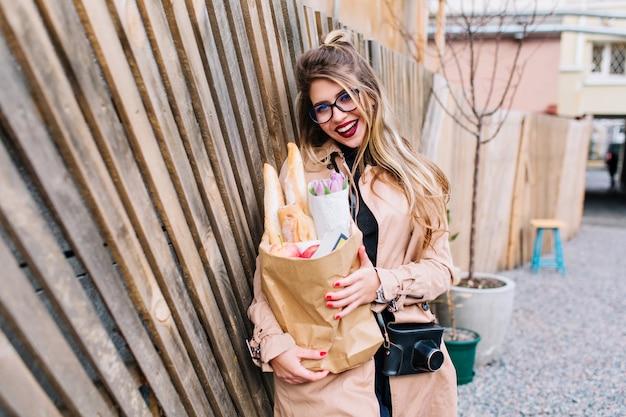 Attraktives mädchen mit langen haaren, die mit dem einkaufen zufrieden waren, lehnte sich gegen den holzzaun. stilvolle junge frau in der braunen kleidung, die mit tasche vom lebensmittelgeschäft aufwirft und auf dem straßenhintergrund lacht.