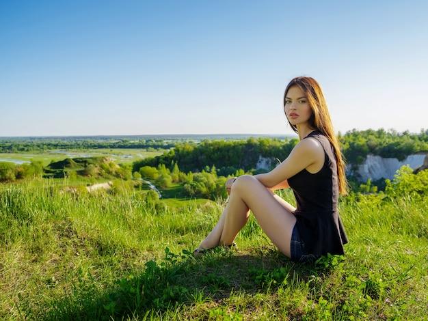 Attraktives mädchen mit langen haaren entspannt sich im freien. junge frau, die durch eine klippe draußen auf natur sitzt. weibliches modell, das in einem feld an einem sonnigen sommertag aufwirft.