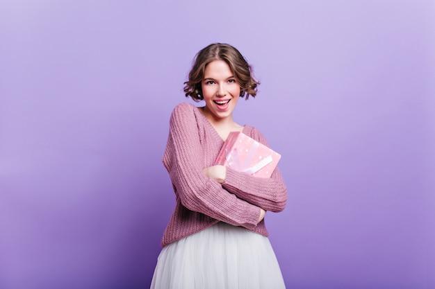 Attraktives mädchen mit lockiger frisur, die neujahrsgeschenk hält und lächelt. elegante frau im weißen rock posiert mit rosa geschenkbox auf lila wand.