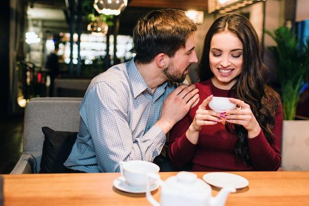 Attraktives mädchen sitzt auf dem sofa im restaurant und trinkt tee, während ihr partner seine hand über ihre schulter gelegt hat und zu ihr schaut. sie lächelt.