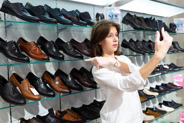 Attraktives mädchen wählt die schuhe ihres mannes für ein geschäftstreffen und ruft ihn in einer boutique am telefon an