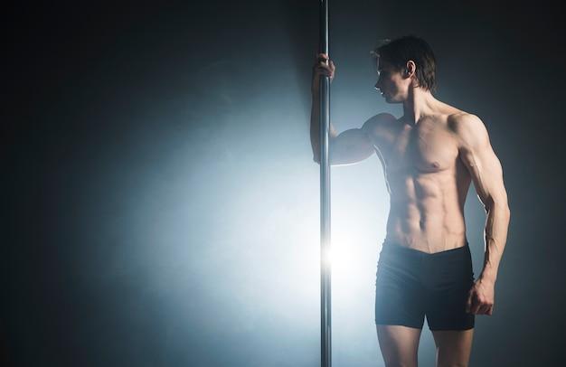 Attraktives männliches baumuster, das einen stangentanz durchführt