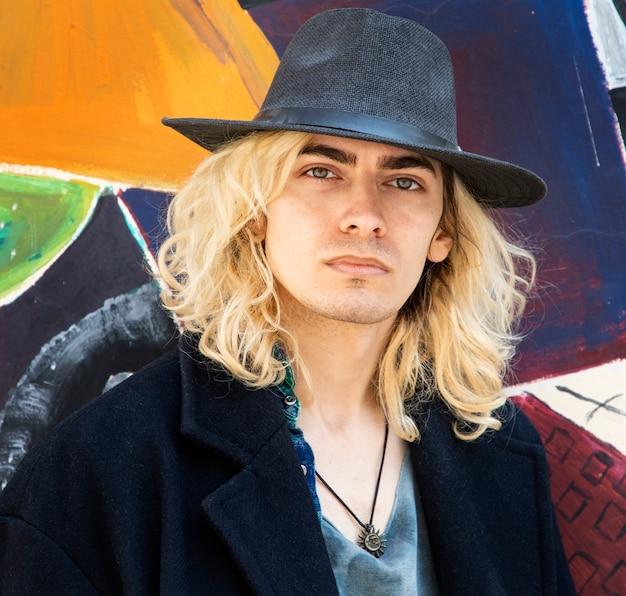 Attraktives männliches blondes modell, das einen hut trägt
