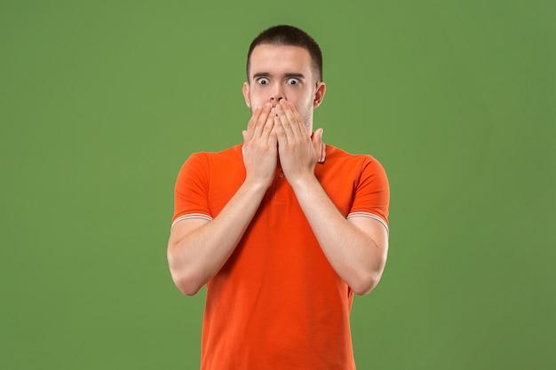 Attraktives männliches halbes vorderes porträt auf grünem studiohintergrund. junger emotional überraschter bärtiger mann stehend.